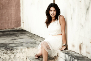 Gina Rodriguez posed for a photo, sitting on a ledge against a fence