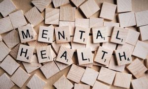 Scrabble pieces spell out mental health.